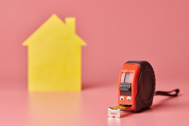 Concepto divertido de renovación de casa. cinta métrica de metal y otros artículos de reparación. reparación del hogar y concepto redecorado.