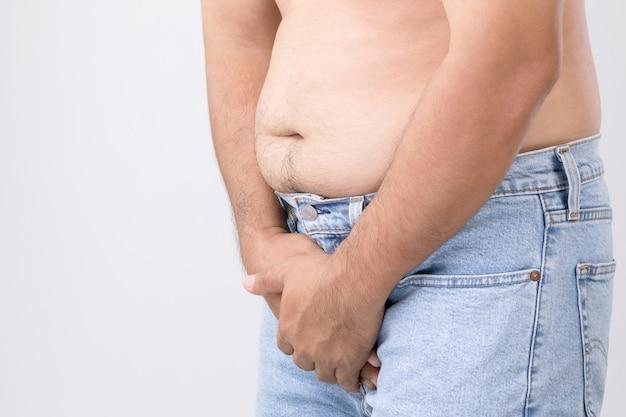 Concepto de dolor en el pene: el hombre usa sus manos para presionar su pene en la pared gris. utilizado para el cáncer de próstata