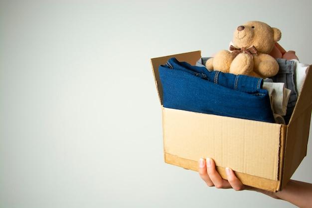 Concepto de donación. manos sosteniendo la caja de donar con ropa. copia espacio