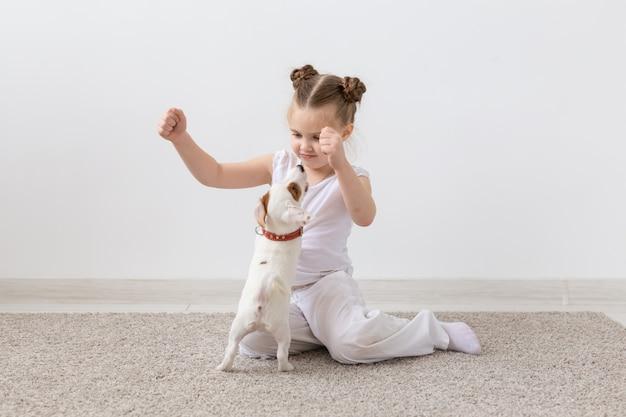 Concepto de dueño, niños y perros de la mascota - niña sentada en el suelo con lindo cachorro de jack russell terrier y jugando
