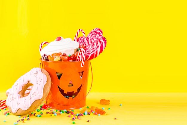 Concepto de dulces de halloween, cubo con dulces