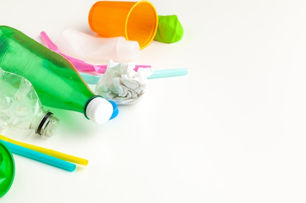 Concepto de ecología de peligro de residuos plásticos con basura y coloridas pajitas de un solo uso, tazas de cubiertos, botellas sobre fondo blanco.