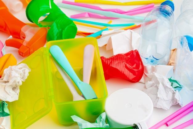 Concepto de ecología de peligro de residuos plásticos con basura y coloridas pajitas de un solo uso, tazas de cubiertos, botellas