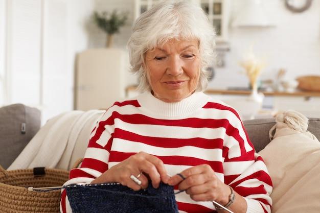 Concepto de edad, ocio, afición y jubilación. atractiva y elegante pensionista caucásica en suéter rojo blanco a rayas sentado en el sofá en un interior acogedor con agujas e hilo, bufanda de tejer o sombrero