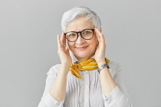 Concepto de edad, óptica, gafas y visión. sonriente mujer madura jubilada elegante con expresión facial alegre, ajustando elegantes anteojos en marco negro, vistiendo camisa y bufanda