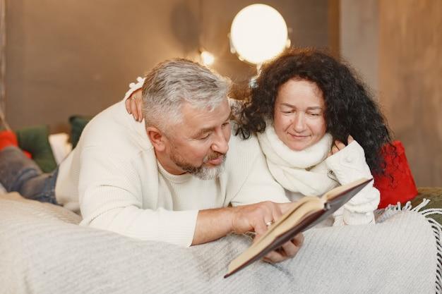 Concepto de edad y personas. pareja mayor en casa. mujer con un suéter de punto blanco.