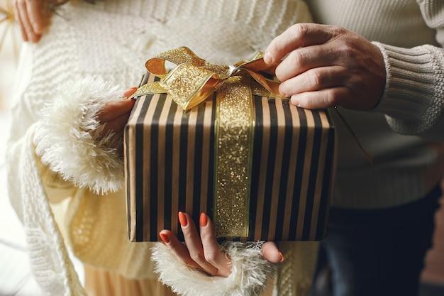 Concepto de edad y personas. pares mayores con caja de regalo sobre fondo de luces. mujer en una sudadera de punto blanco.