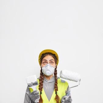 Concepto de edificación y construcción. mujer sorprendida con dos coletas usa máscara protectora y casco vestido en poses uniformes con equipo de construcción enfocado arriba aislado sobre pared blanca
