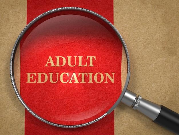 Concepto de educación para adultos. lupa sobre papel viejo con línea vertical roja.