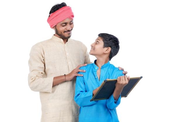 Concepto de educación: agricultor indio con su colegial sobre fondo blanco.
