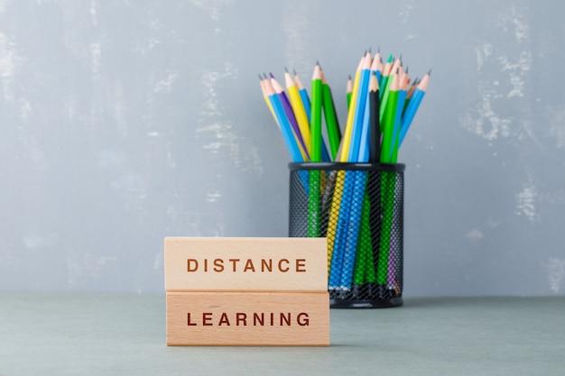 Concepto de educación a distancia con bloques de madera con palabras, vista lateral de lápices de colores.