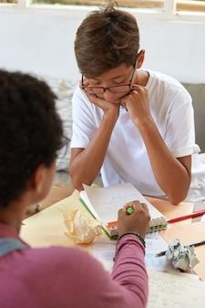 Concepto de educación, enseñanza y aprendizaje. la hermana mayor explica cómo hacer la tarea al hermano que estudia en la escuela, señala notas en un diario en espiral, se sienta en el espacio de trabajo compartido. formación docente y alumno