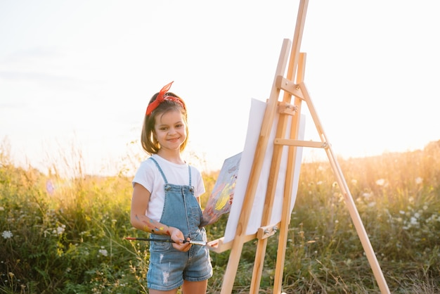 Concepto de educación, escuela, arte y pintura - cuadro de pintura de niña estudiante