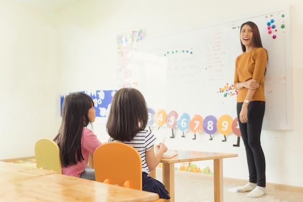 Concepto de la educación, de la escuela primaria, del aprendizaje y de la gente - grupo de niños de la escuela con el profesor que se sienta en sala de clase. imágenes de estilo de efecto vintage.