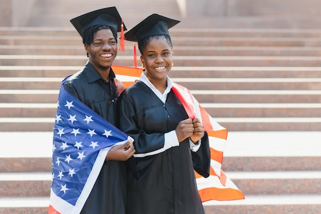 Concepto de educación, graduación y personas: estudiantes internacionales felices en juntas de mortero y batas de soltero con bandera estadounidense