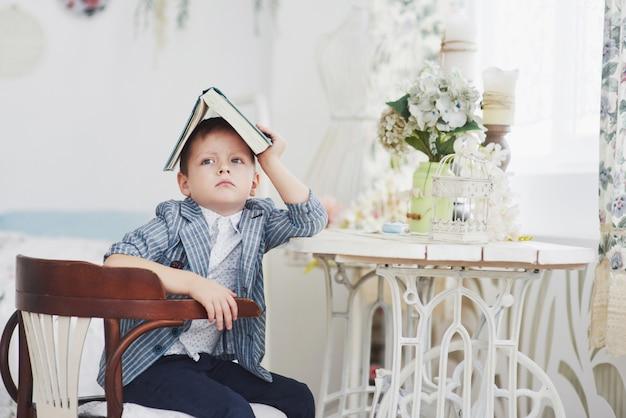 Concepto de educación, infancia, personas, tareas y escuela: libro de lectura o libro de texto de chico estudiante aburrido en casa