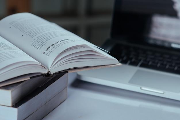 Concepto de educación, libros y computadora portátil en la biblioteca