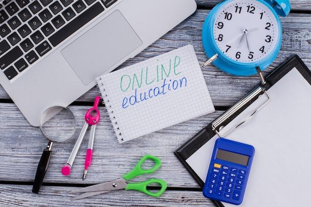 Concepto de educación en línea. elementos planos para estudiar. pc portátil con portapapeles y otros accesorios de papelería en mesa de madera blanca.
