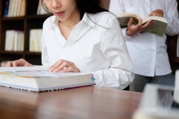 Concepto de educación, mujer joven leyendo un libro de texto en la universidad de la biblioteca.