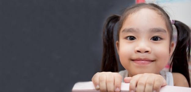 Concepto de educación - niña feliz con dibujo de tiza cálculos matemáticos en bla