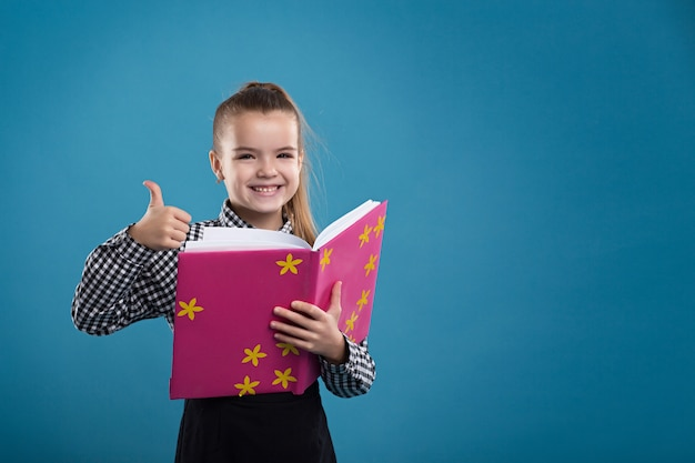 Concepto - educación. niña leyendo un libro en una portada rosa