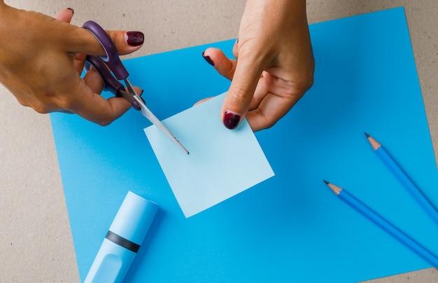 Concepto de educación con útiles escolares en papel, plano lay. mujer cortando nota adhesiva.