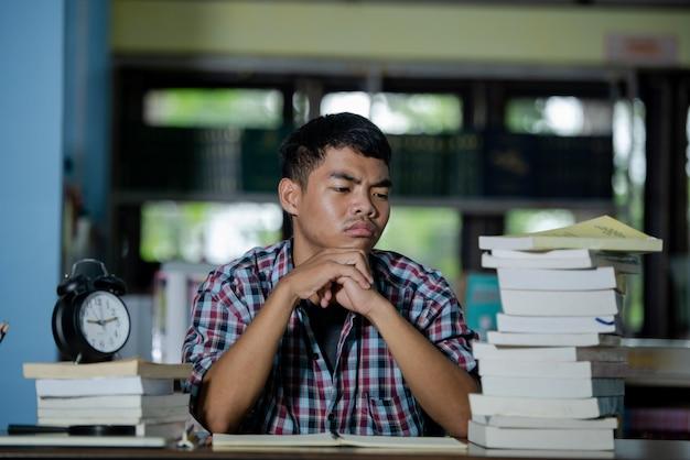 Concepto educativo: estudiante cansado en una biblioteca