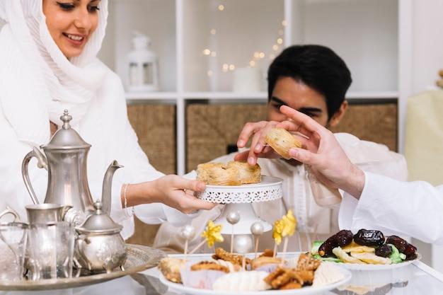 Concepto de eid al-fitr con con gente comiendo en mesa