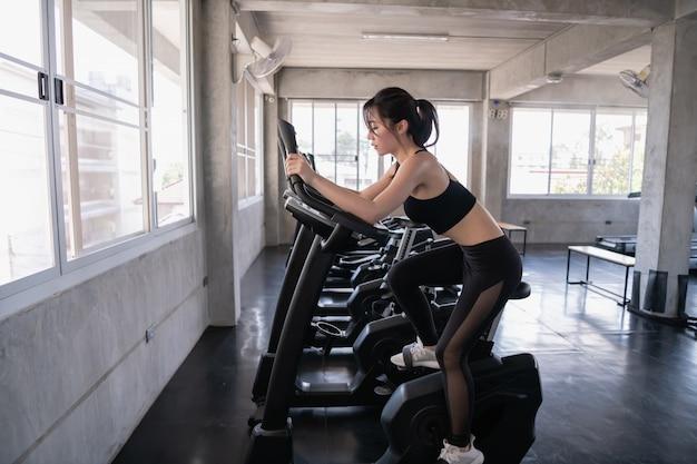 Concepto de ejercicio muchacha hermosa que ejercita con una bicicleta de ejercicio de giro. muchacha hermosa que ejercita muslos para las proporciones hermosas.