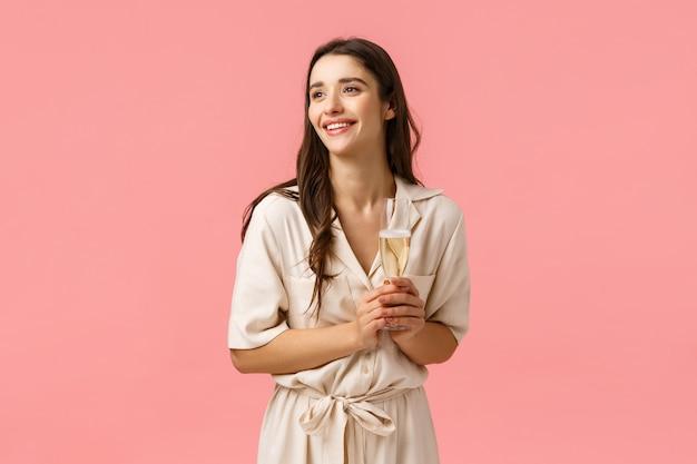 Concepto de elegancia, romance y ternura. encantadora mujer morena bonita en vestido encantador contemplando la hermosa ceremonia de boda, siendo una fiesta de invitados, sosteniendo una copa de champán y sonriendo