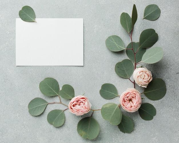 Concepto elegante de hojas y rosas con tarjeta vacía