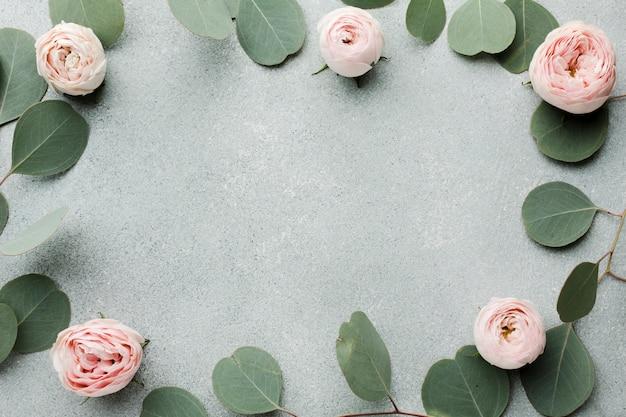 Concepto elegante marco de hojas y rosas con espacio de copia
