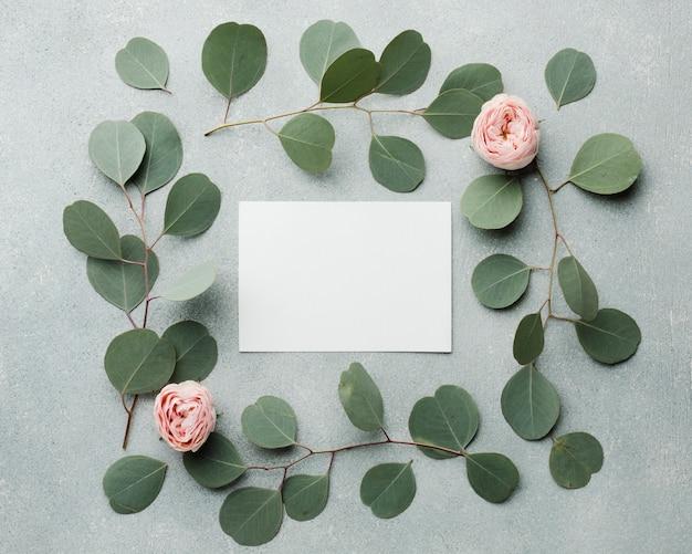 Concepto elegante marco de hojas y rosas con tarjeta vacía