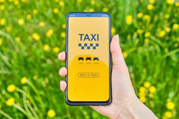Concepto de elegir un tipo de economía de taxi, estándar, negocios en un teléfono inteligente sobre un fondo de hierba.