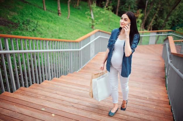 Concepto de embarazo, maternidad, personas y expectativas - cerca de la mujer embarazada con bolsas de compras en el parque