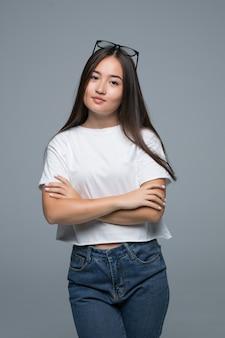 Concepto de emoción retrato de mujer asiática linda enojada de pie posando con los brazos cruzados mirando a la cámara con ropa gris sobre un fondo blanco