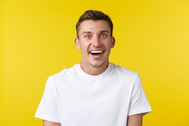 Concepto de emociones de estilo de vida, verano y personas. primer plano de chico guapo sorprendido super feliz recibir noticias impresionantes, levantar las cejas asombrado y sonriente, de pie fondo amarillo.
