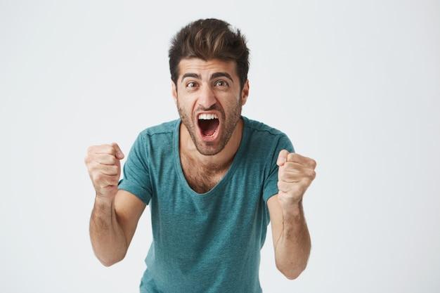 Concepto de emociones y logros. disparo de cerca de feliz exitoso estudiante o empleado casualmente gritando con expresión ganadora, puños bombeados, celebrando el éxito en una pared blanca