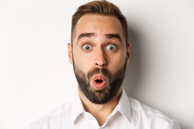 Concepto de emociones y personas. disparo en la cabeza del hombre expresa sorpresa y asombro, diciendo wow, de pie