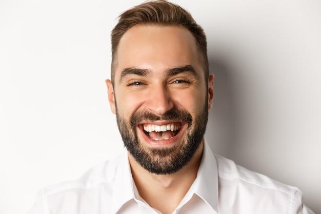 Concepto de emociones y personas. foto de cabeza de hombre atractivo feliz riendo y sonriendo, exprese regocijo