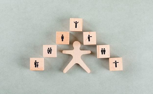 Concepto de empleado de éxito con humanos de madera, bloques con iconos.