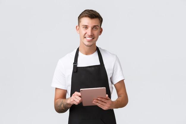 Concepto de empleados de cafetería y cafetería de pequeñas empresas guapo carismático camarero barista sonriente en el fondo blanco.