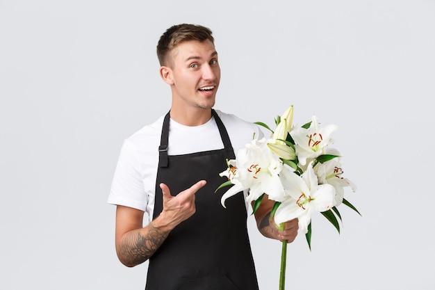 Concepto de empleados y minoristas de pequeñas empresas vendedor guapo en delantal negro que señala con el dedo a la floristería de flores hermosas en la tienda que vende lirios sonriendo amistosamente a la pared blanca del cliente