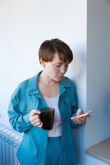 El concepto de empleo, entrevistas, publicidad de tecnología digital - mujer tomando café y hablando por teléfono. mujer sonriente con taza hace una llamada. mañana de niña