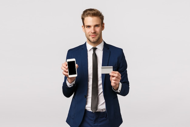 Concepto empresarial, corporativo y financiero. feliz y seguro hombre de negocios rico en traje clásico, con tarjeta de crédito y pantalla de teléfono inteligente, promueve el sistema bancario, paga en línea, compra