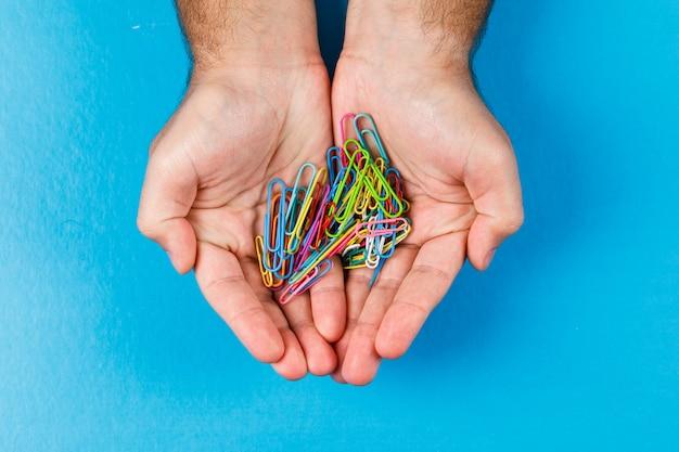 Concepto empresarial y financiero con clips de papel en la palma sobre fondo azul plano lay.