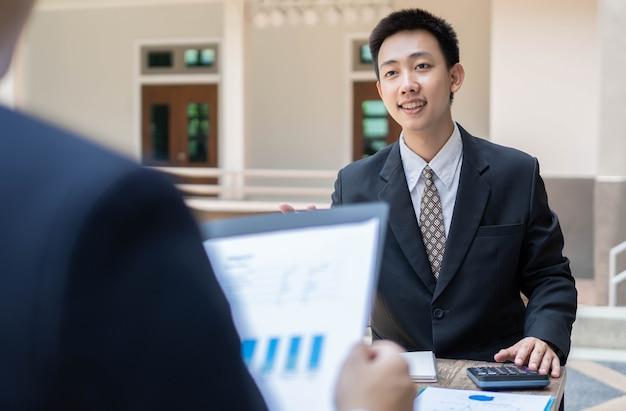 Concepto de empresario los trabajadores de oficina masculinos que trabajan en la tarea de contabilidad con la calculadora y la computadora portátil dentro del edificio.