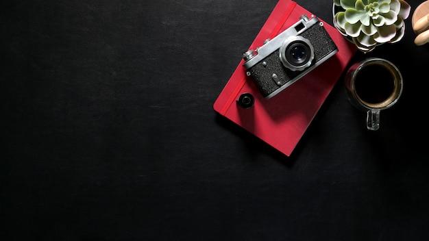Concepto de encabezado web, escritorio de cuero oscuro con cámara vintage, cuaderno rojo y espacio para copiar
