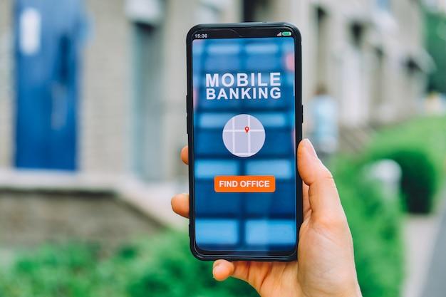 El concepto de encontrar una oficina bancaria en la ciudad. aplicación de interfaz de banca móvil para teléfonos inteligentes en la mano
