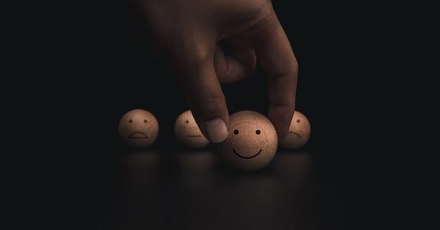 Concepto de encuesta de evaluación, calificación, retroalimentación y satisfacción del servicio al cliente. mano que sostiene la cara de emoticon sonrisa feliz y caras tristes borrosas en bola de madera sobre fondo oscuro.